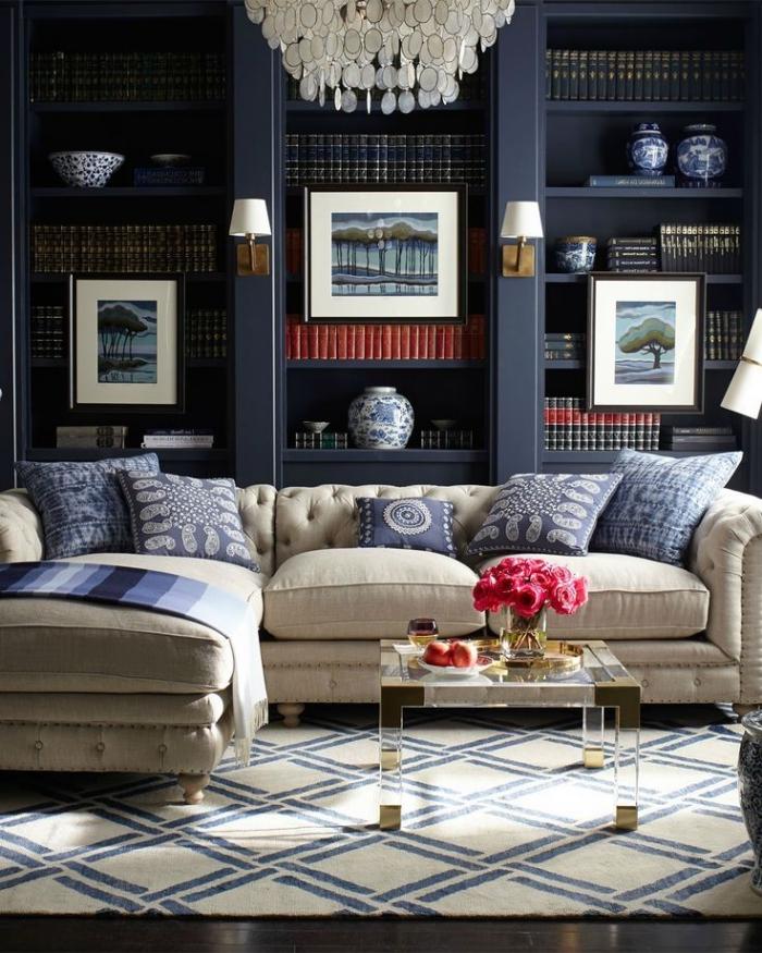 wohnzimmer ideen, großer kronleuchter, rosa blumen, blauer schrank mit vielen regalen, dekokissen in weiß und dunkelblau