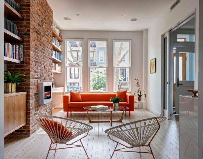 orangenfarbiges sofa, wohnzimmer ideen modern, ziegelwand mit kamin, geflochtene stühle