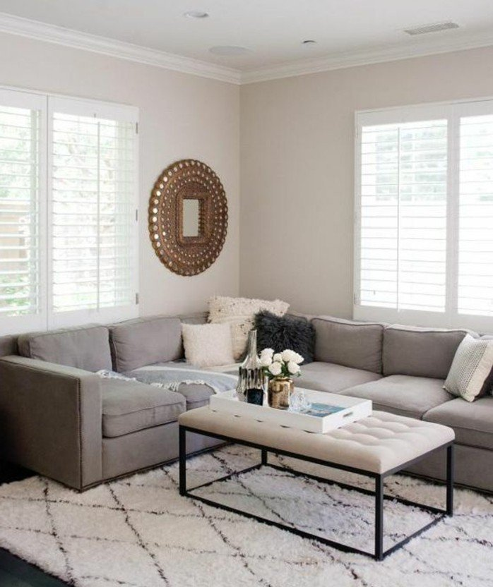 ein graues Ecksofa, weißer Teppich mit geometrischen Motiven, ein weißer Tisch, ein goldener Spiegel