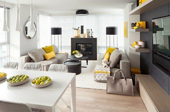 Wohnzimmer in Grau Weiß nach Feng Shui eingerichtet, ein schwarzer Kamin, gelbe Kissen auf graue Sofas