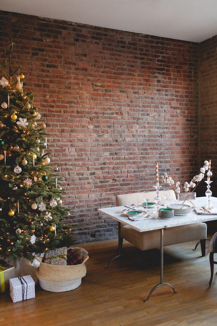 Minimalistische Einrichtung im Wohnzimmer, echter Weihnachtsbaum geschmückt mit bunten Christbaumkugeln