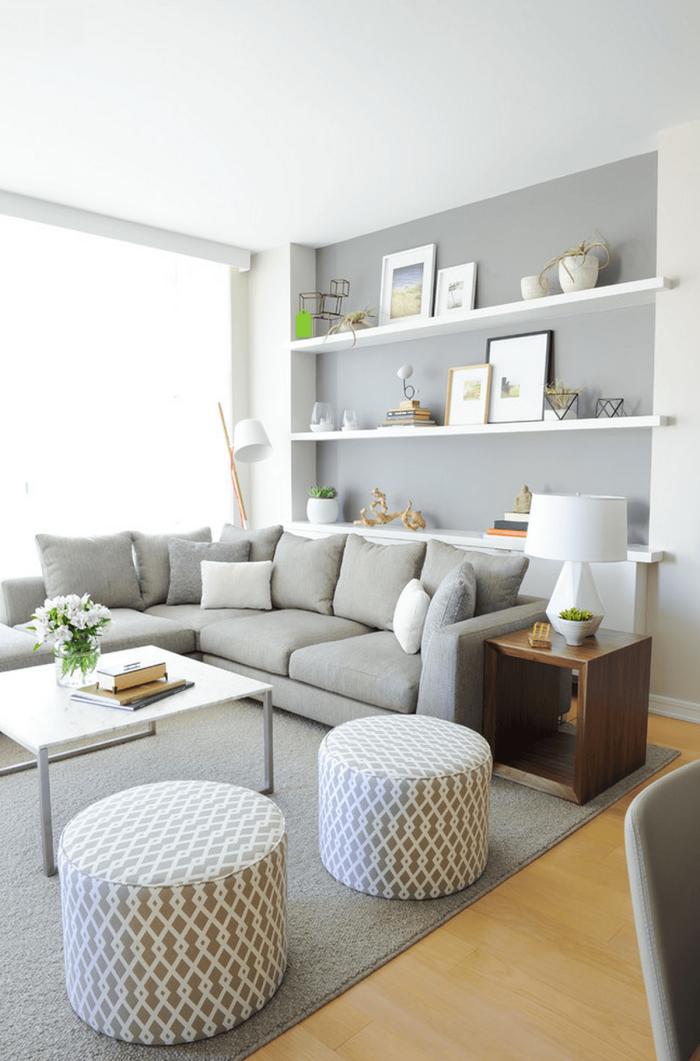 hocker mit geometrischen mustern, wohnzimmergestaltung in hellgrau, regale mit dekoartikeln