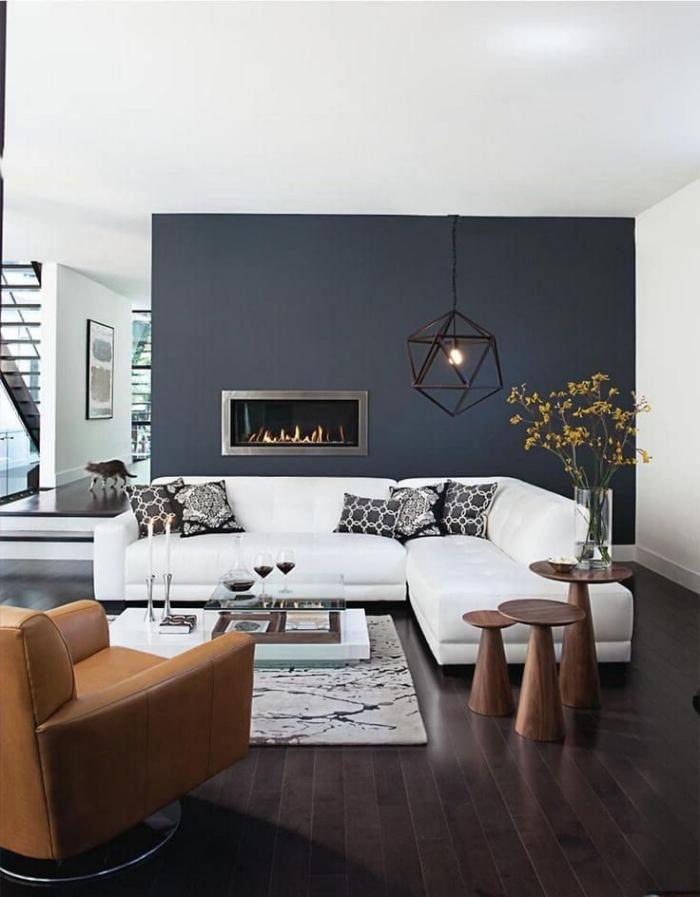 wohnzimmergestaltung in grau und wieß, geometrische leuchte, runde tische aus holz set