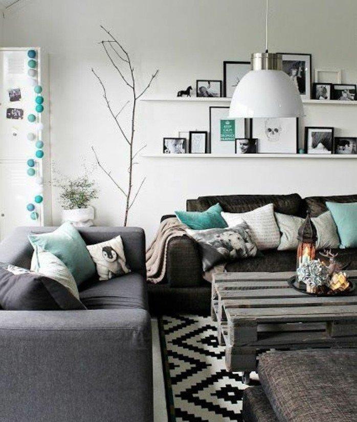 graues Sofa und schwarzes Sofa mit grünen Kissen, zwei Leistne mit vielen Bildern, Wohnzimmer Weiß Grau