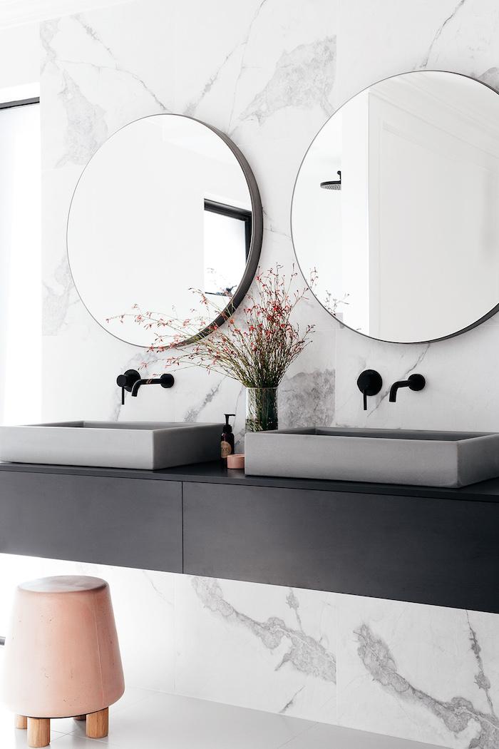 kleiner stuhl und zwei spiegel und graue waschbecken im badezimmer, eine kleine vase mit blumen und grünen blättern