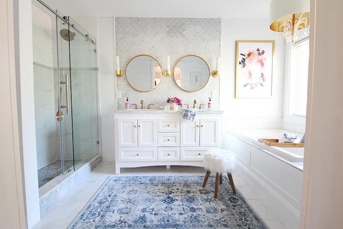 großer blauer teppich und ein kleiner weißer stuhl im badezimmer mit zwei spiegeln und badezimmer regalen, badezimmer mit weißen fenstern