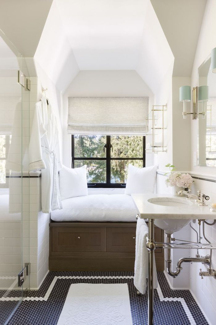 großes badezimmer mit sofa und weißen kissen und einem kleinen fenster, boden aus blauen und weißen fliesen und ein weißes waschbecken