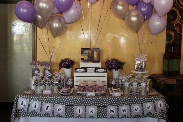 50 Geburtstag Frau, lila Ballons, viele Süßigkeiten, schwarze Ziffer mit 50, das Leben ist süß,