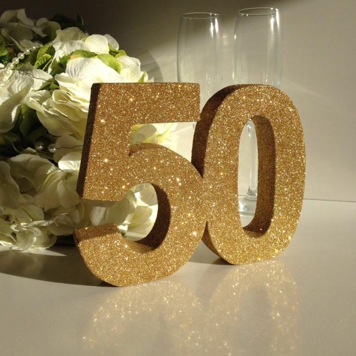 50 Geburtstad Mann, zwei Ziffer mit goldenen Glittern bedeckt, zwei Champanien Gläser, weiße Blumen