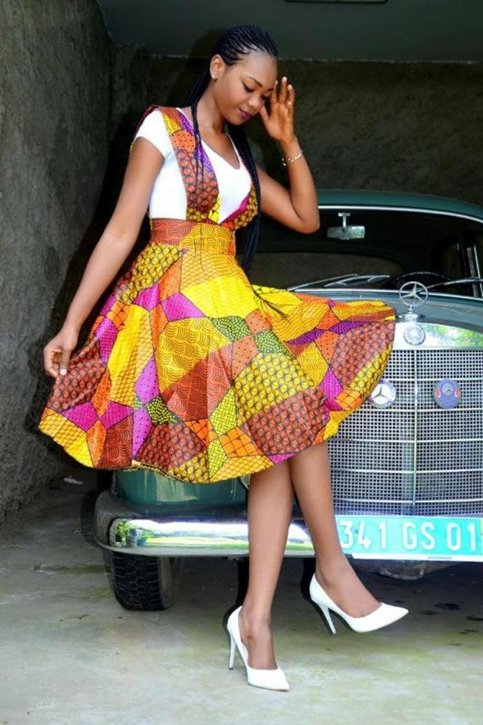 farbtechnik für stoffe, buntes kleid mit gelb, orange, lila, rosa, weiße absatzschuhe, weißer top, mercedes im hintergrund