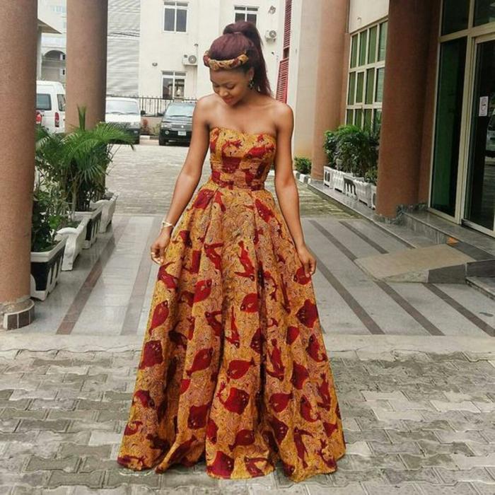 offizielle traditionelle afrikanische kleidung, die heute ganz modern erscheint, dunkelgelbes kleid mit roten motiven schafen das gefühl für eine afrikanische königin