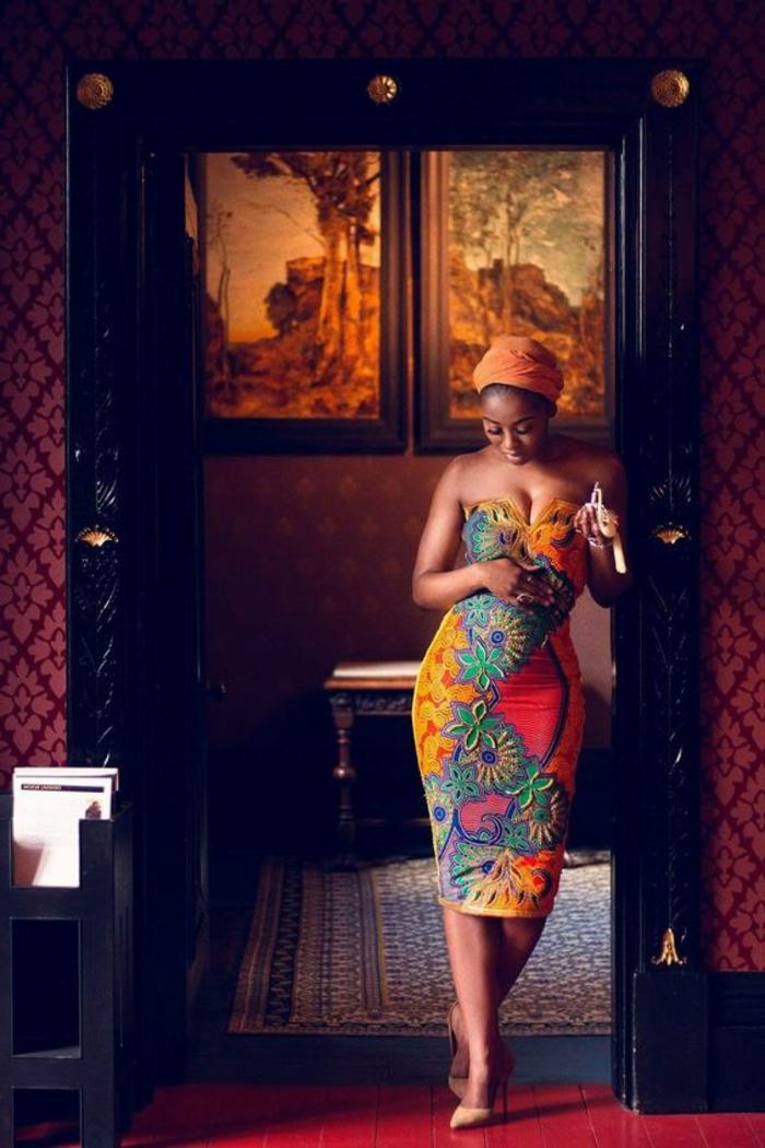 afrikanische kleider zum inspirieren, ein bild von einer frau im luxuszimmer, die model trägt buntes afrokleid und orangenes kopftuch