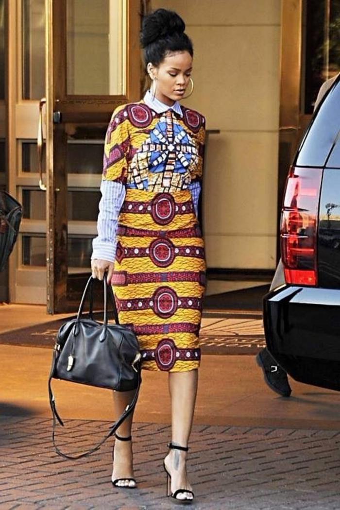 traditionelle afrikanische kleidung, eine der liebsten trends von rihanna, gelb rotes kleid mit blauen motiven am brust, schwarze tasche harminiert mit den schwarzen haaren
