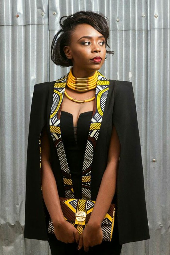 kreative und moderne afrikanische muster zum entlehnen. eine frau fertig zum besonderen anlass, schwarzer eleganter stil mit bunten afro dekorationen, clutch
