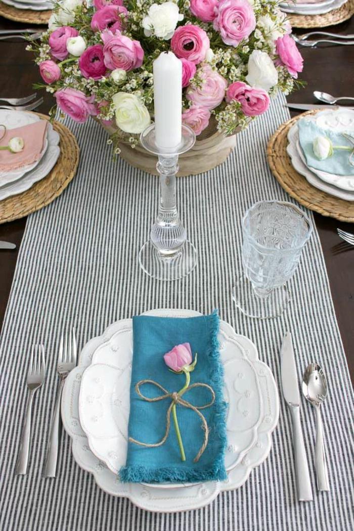 zwei weiße Teller, eine blaue Serviette, rosa Blumen, ein schwarz weißer Tischläufer, eine weiße Kerze, Geburtstagsdeko