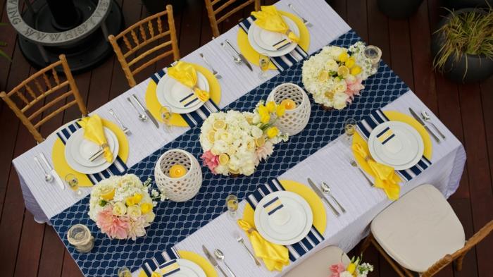 blauer Tischläufer, gelbe Untersilien, gelbe Servietten, weiße Blumen und Zitronen, Geburtstagsdeko