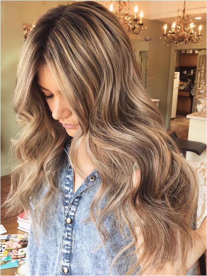 strähnchen blond, eine junge frau mit haare mit langen blonden strähnchen und mit einer blauen jacke, damen frisuren trends