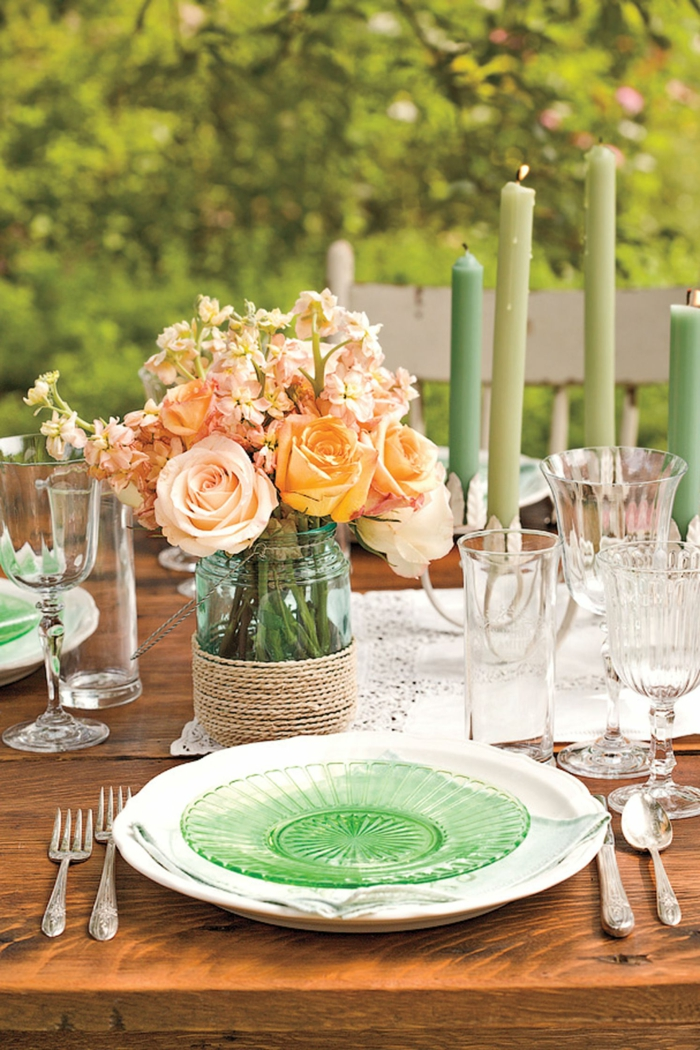 viele grüne Kerzen, orange Rosen in rustikale Vase, Teller aus Glas, ein Tisch aus Holz, Geburtstagsdeko