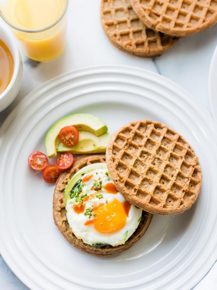 brunch ideen, sandwich aus waffeln, avocado und eiern, cherry tomaten, gesunder frühstück