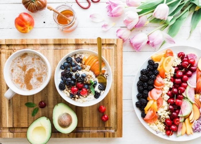 brunch rezepte, weiß rosa tulpen, geshcnittene avocado, gesunder frühstück mit haferflocken und obst