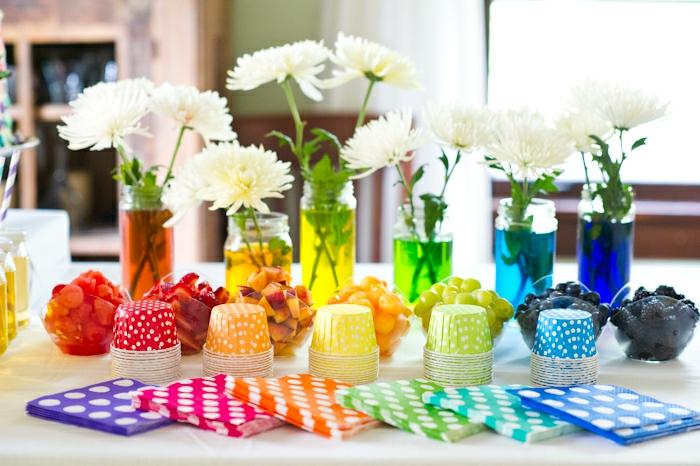 weiße Blumen, sechs Vasen mit bunten Flüssigkeiten darin, bunte Servietten, bunte Becher, Blumen Tischdeko aus Glas
