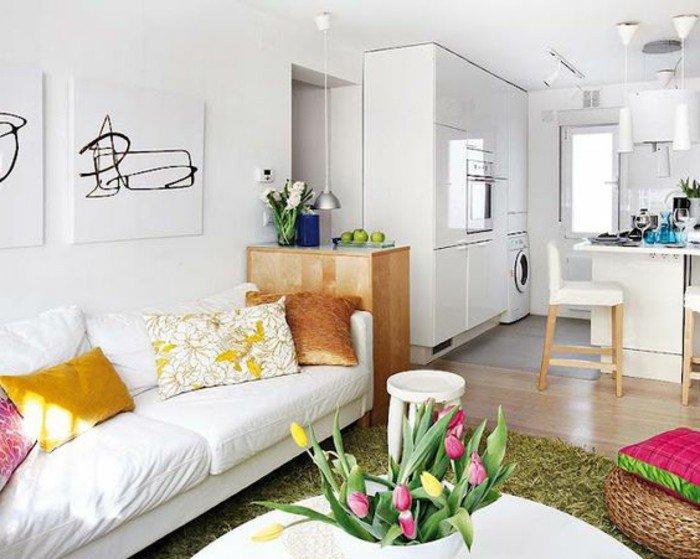 Kleines Wohnzimmer einrichten, weißes Sofa, bunte Kissen, ein runder Stuhl, Vase mit Tulpen
