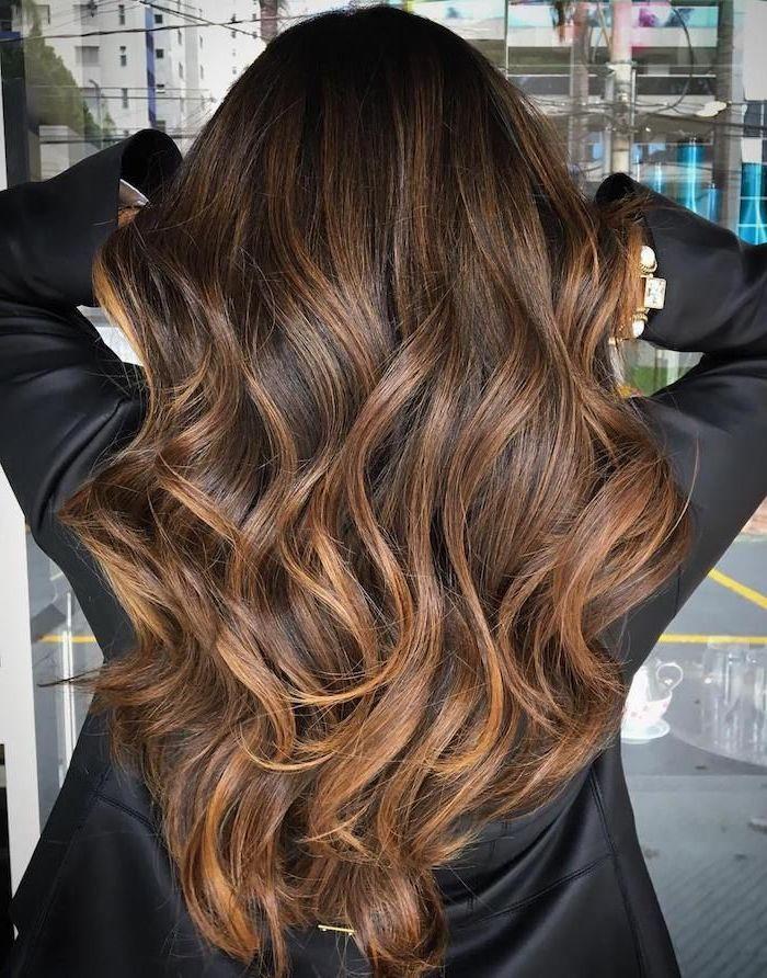 lange braune haare einer jungen frau mit einer schwarzen jecke aus ledder, braune haare mit braunen strähnchen