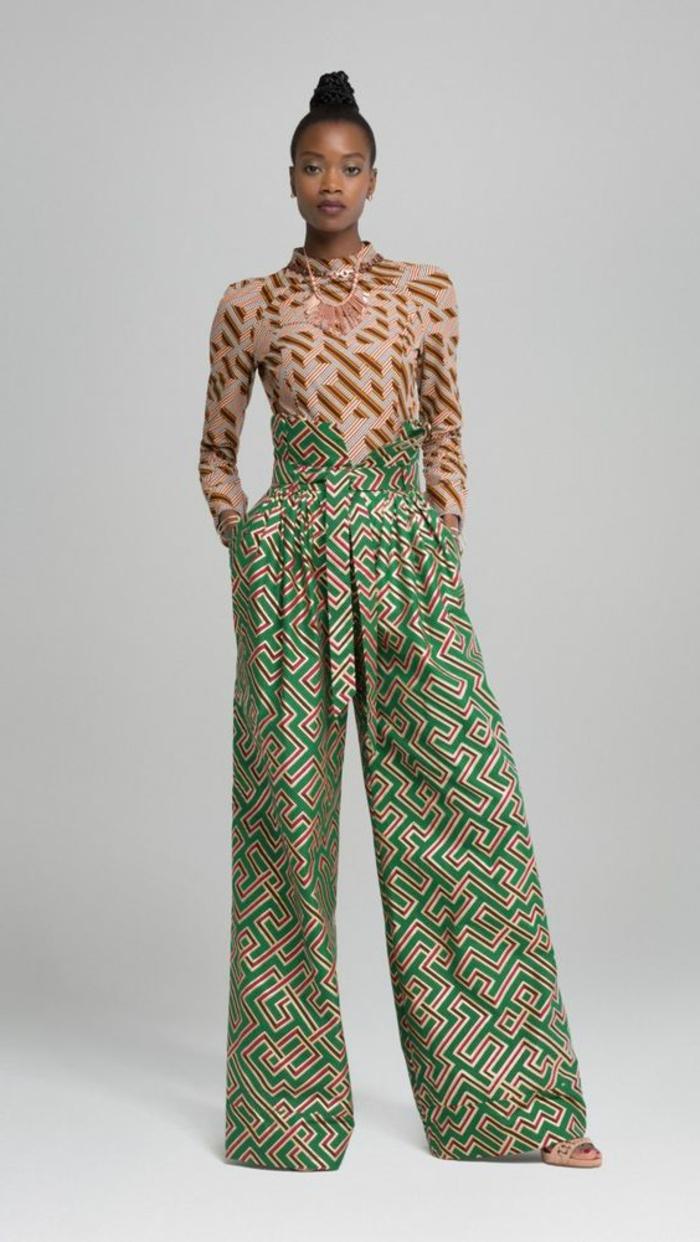 afrikanische mode, kombination von verschiedenen mustern, grün beige geometrische formen an den hosen und braune bluse mit rosegold motiven
