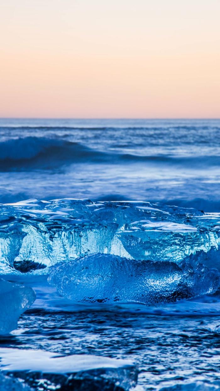 ein Eisberg, in dem Meer, fast zerschmolzen, rosa Himmel, schöne Hintergrundbilder, Wellen