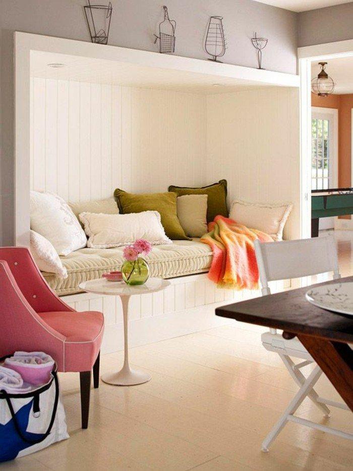 ein Sofa in der Wand eingebaut, rosa Sessel und kleiner Tisch, eine Leseecke, kleines Wohnzimmer einrichten