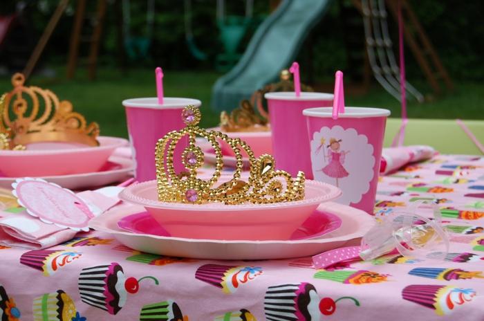 ein Kindergeburtstag, rosa Becher mit Prinzessinnen, eine goldene Krone, bunte Tischdecke mit Süßigkeiten versehen, Geburtstagsdeko