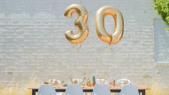zwei Ballons mit den Ziffern drei und null, eine Ziegelmauer, Tischdeko mit Kakteen, Geburtstagsdeko für dreißigsten Geburtstag