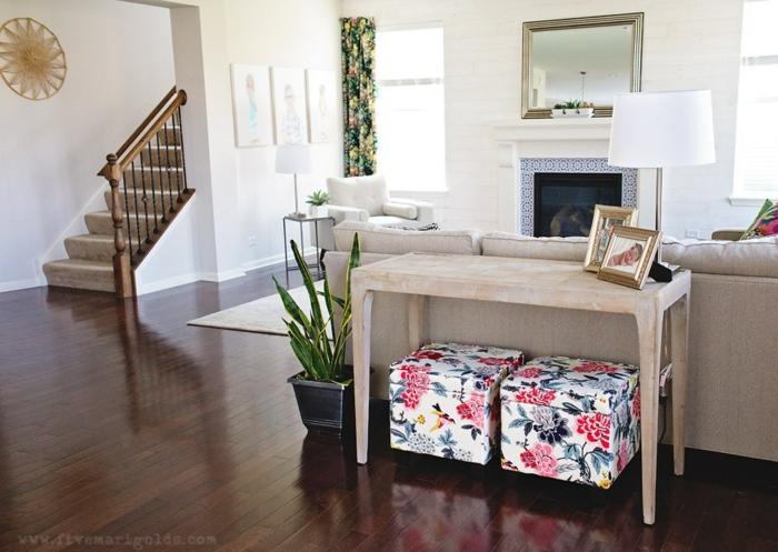 braune glänzende Diele, ein Kamin und ein Spiegel, ein Tisch aus Holz, bunte Hocker, Wandgestaltung für Wohnzimmer