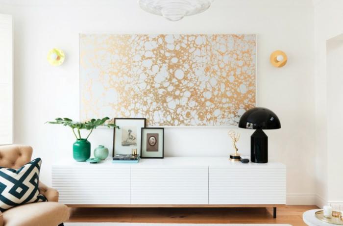 Wandgestaltung für Wohnzimmer, ein großes Bild mit goldfarbene abstrakte Motive, ein weißes Regal, schwarze Tischlampe