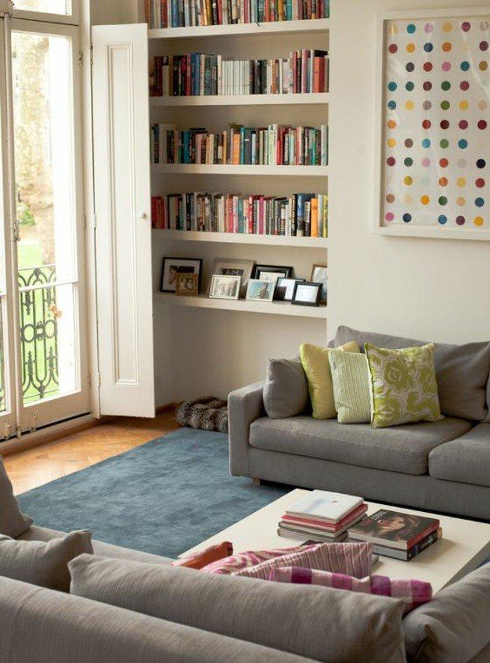 ein buntes Bild an der Wand, Bücherregal mit bunten Bücher, zwei graue Sofa, ein weißer Tisch, eine Einrichtung nach Feng Shui, Wohnzimmer Wohnideen