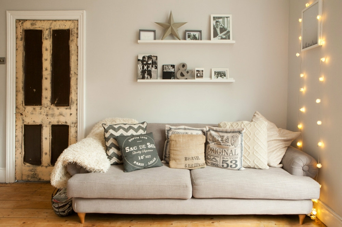 weiße Wandfarbe, eine Lichterkette, ein beiges Sofa, einige bunte Kissen, Bodendiele, Wanddeko Wohnzimmer