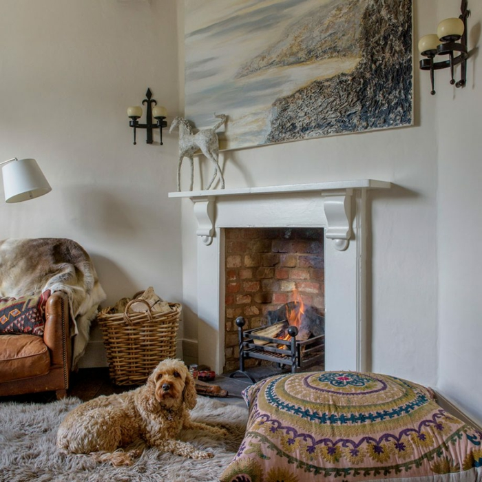 weiße Wandfarbe, ein Teppich, maritimes Bild als Wanddeko Wohnzimmer, ein weißer Kamin