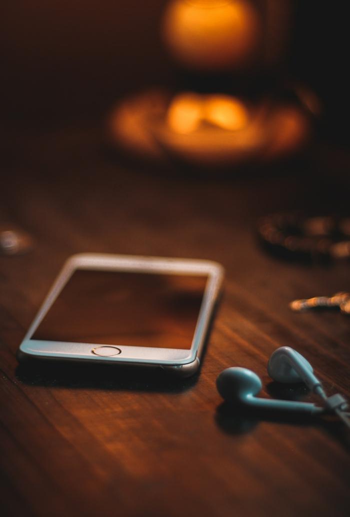 ein geheimsvolles Bild von einer Kerze, ein Handy auf dem Tisch, Kopfhörer, schöne Handy Hintergrundbilder