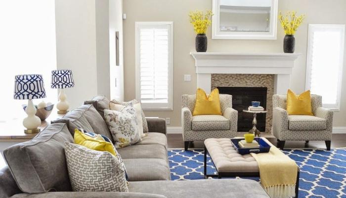 ein blauer Teppich, ein beiges Sofa, gelbe Kissen, zwei schwarze Vasen, Wanddeko Wohnzimmer