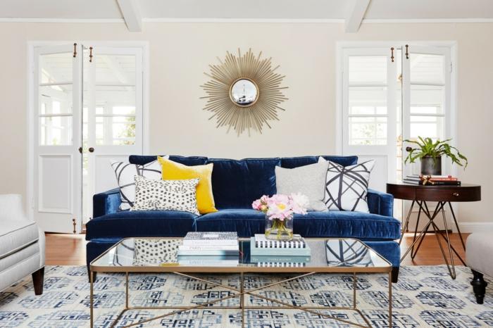 Wanddeko Wohnzimmer, ein Spiegel mit Strahlen wie die Sonne, ein dunkelblaues Sofa, ein alter Teppich