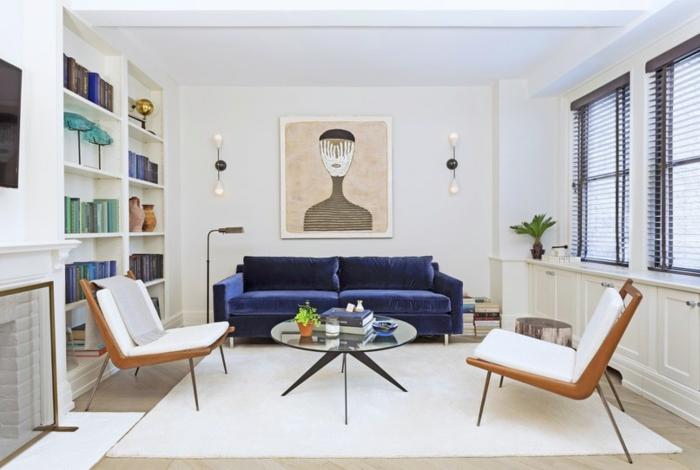 ein weißer Teppich, ein blaues Sofa, ein kleiner runder Tisch aus Glas, zwei Sessel, weiße Wandfarbe