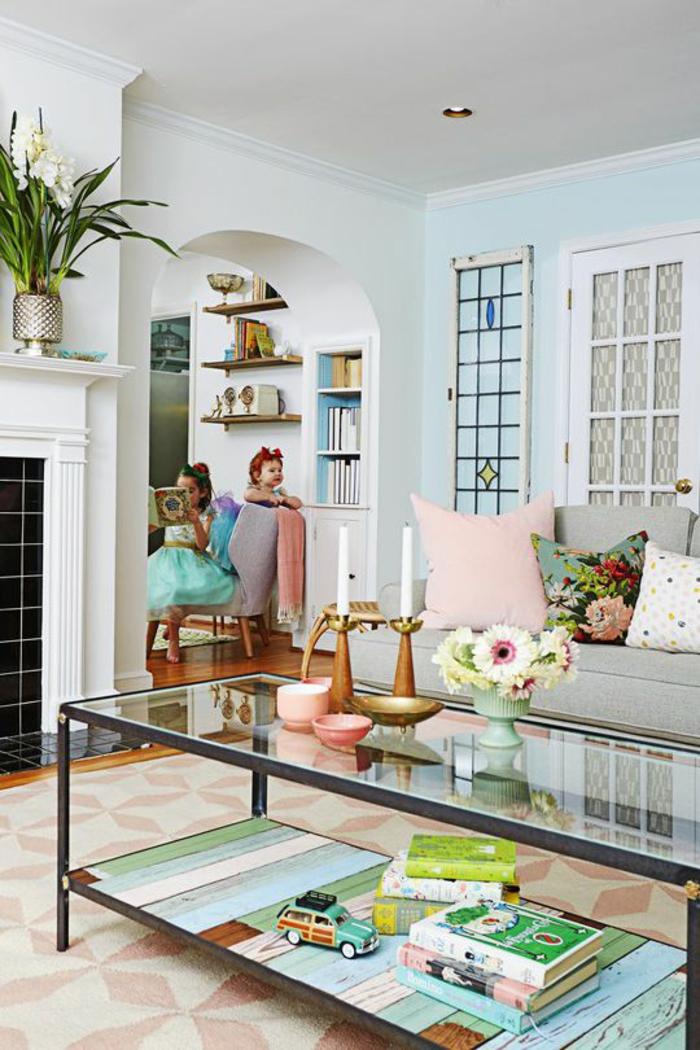 ein graues Sofa, ein Tisch aus Glas, rosa Kissen, bunte Kissen, Wanddeko Wohnzimmer, zwei Schwesterchen