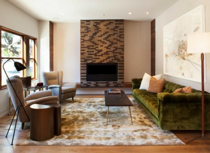 ein grünes Sofa, ein brauner Teppich, zwei braune Sessel, eine Fernsehwand mit Backstein Optik, Wanddeko Wohnzimmer