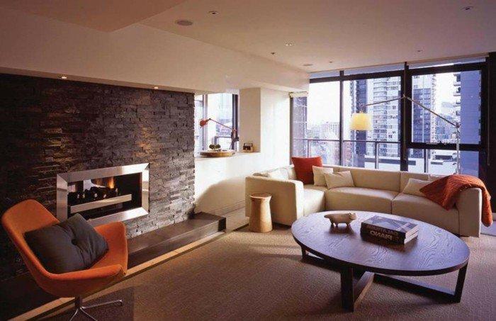 ein roter Sessel, ein runder Tisch, Laminat Boden, ein Kamin mit Feuer, Wohnideen Wohnzimmer