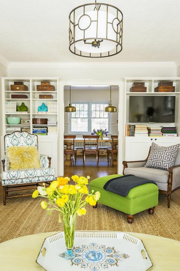 Wohnzimmerwand in weißer Farbe, grauer und weißer Sessel, grüne Hocker, weiße Regale