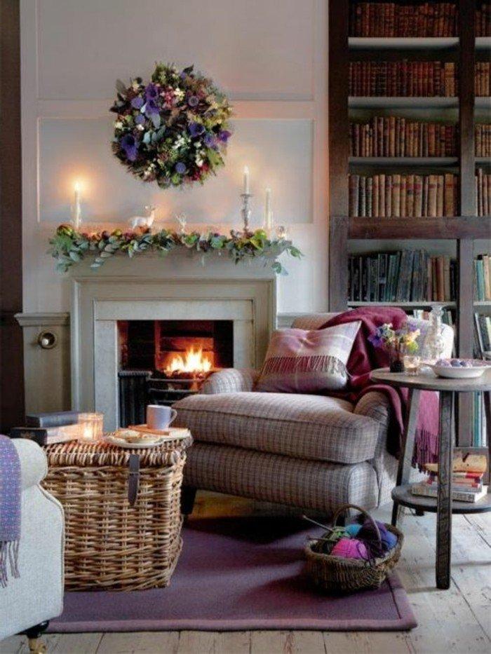 ein grauer Sessel, ein bunter Blumenkranz, eine grüne Dekoration über den Kamin, lila Teppich
