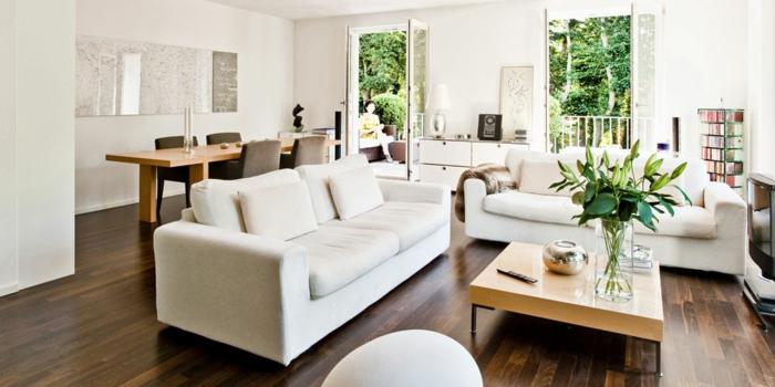 zwei weiße Sofas, Laminat Boden, ein kleiner quadrate Tisch, eine weiße Landkarte, Wohnzimmerwand