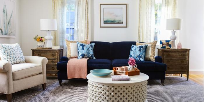 blaues Sofa, ein runder Tisch, ein grauer Teppich, ein weißer Sessel, Wohnzimmerwand mit Wandbilder