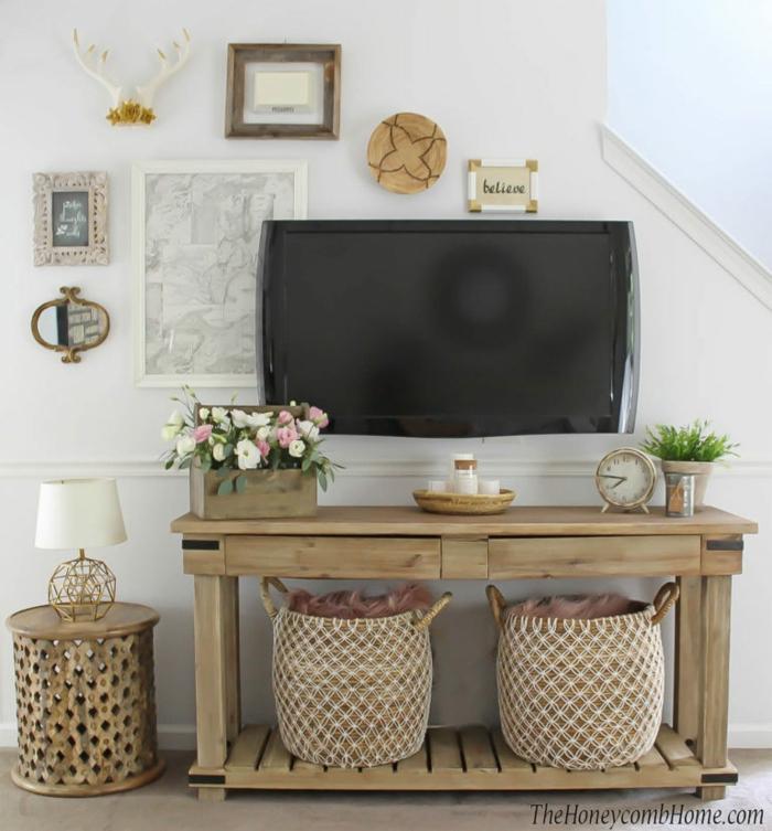 Wohnzimmerwand mit Fernseher, viele verschidene kleine Dekoartikel, ein Regal mit zwei Körben