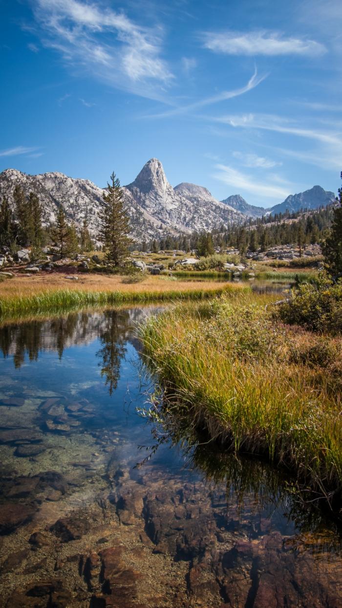 ein blauer Himmel, ein Fluss voller kleine Steine, viel Gras, Bildschirmhintergrund mit Natur